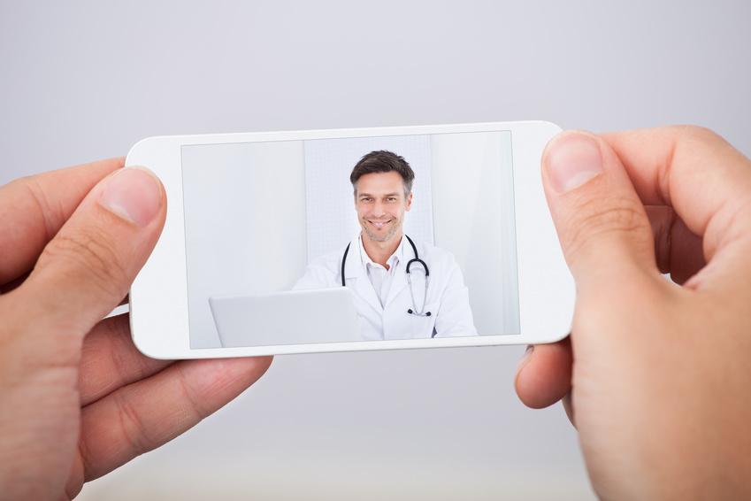 Arzt kommuniziert in der Online sprechstunde via Smartphone mit einem Patienten