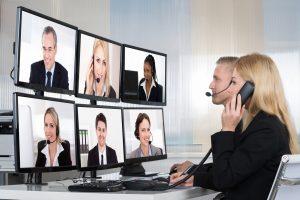 Zwei Mitarbeiterinnen eines Unternehmens schulen per Video Tutorial mehrere Kollegen, die über Monitore zugeschaltet sind